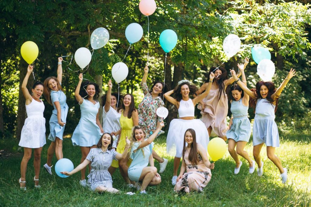 A UK hen do group partying outside in a park with balloons