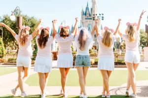 A bride and five bridesmaids standing in front of the Disneyworld castle at the theme park