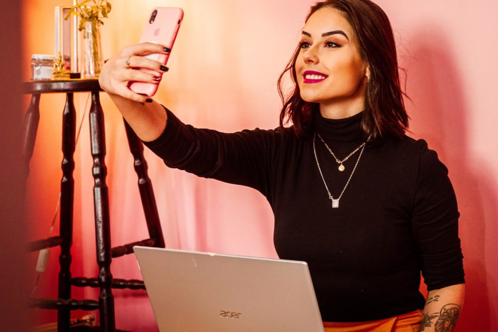 A woman at home on her phone for a virtual hen party