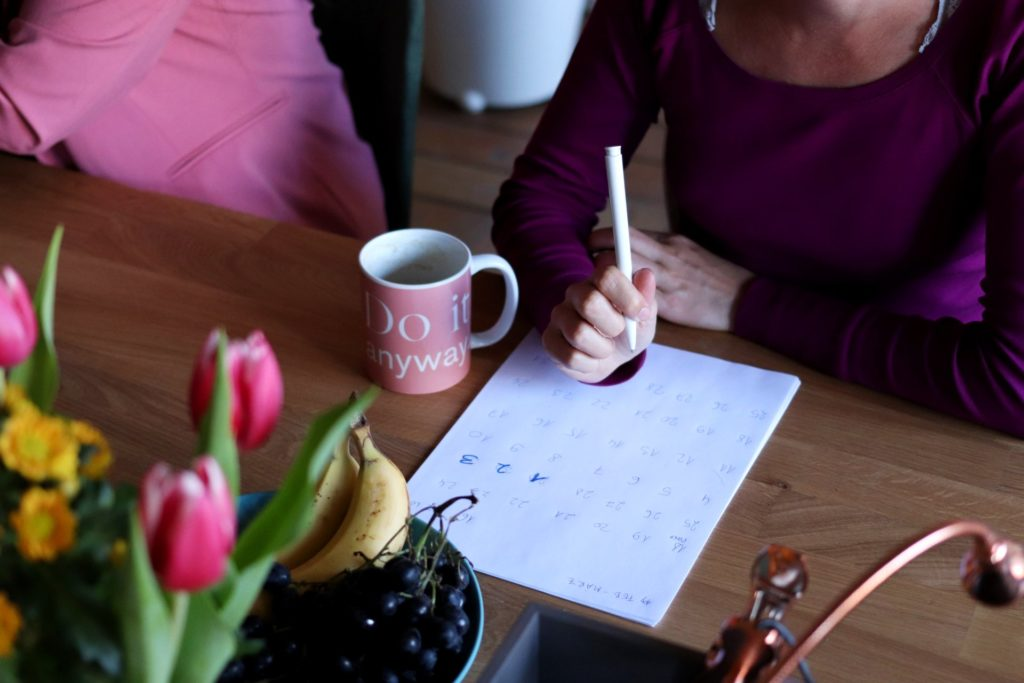 Woman sitting down with a calendar to plan a UK hen do during covid19