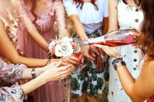 A hen party group celebrating with a glass of wine