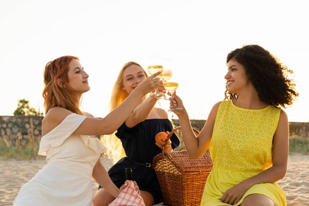 Three women having a beach picnic to invite the bride to her own hen party