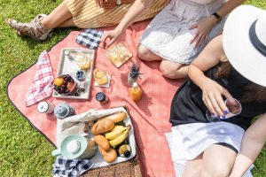 COVID hen party ideas including 3 girls having a picnic outside