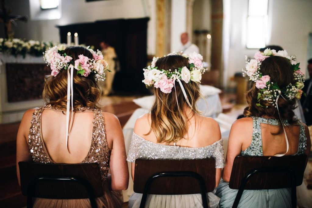 Three bridesmaids sitting in chairs at the wedding ceremony. The maid of honour is thinking about her maid of honour duties for the day.