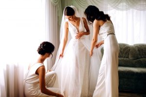 A bride in her wedding dress and two women completing their maid of honour duties