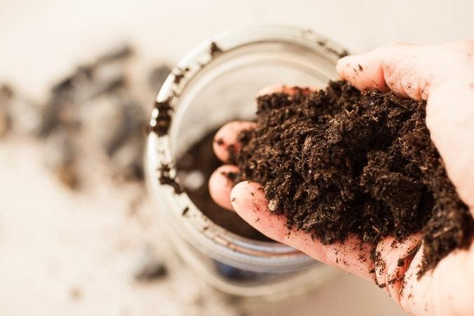 A woman pouring soil into a unity dirt jar